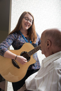 Care Dimensions music therapist Katie Bagley plays guitar for hospice patient