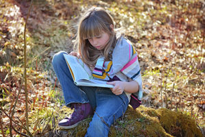 girl reading book coping with death, loss, and grief