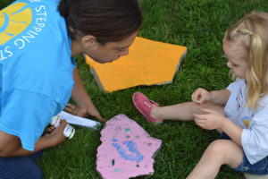 Care Dimensions Camp Stepping stones volunteer and child with puzzle piece