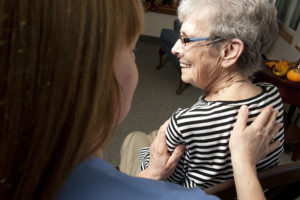 Care Dimensions massage therapist treating upper back of female hospice patient