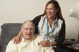 Hospice patient Bill McPherson laughs with his Care Dimensions nurse case manager, Wanda Santana