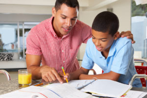 adult male helping boy with homework