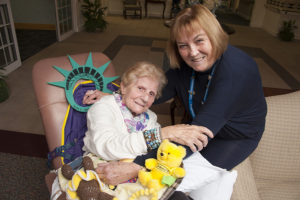Care Dimensions volunteer with female hospice patient in chair smiling