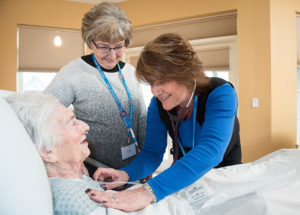 two Care Dimensions hospice nurses caring for female patient in facility