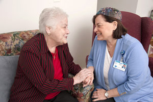 Care Dimensions chaplain Matia Angelou talks with female hospice patient