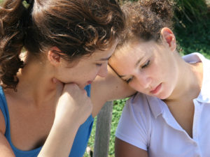 mother helping sad daughter cope with grief