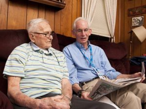 Care Dimensions Veteran-to-Veteran volunteer with hospice patient reviewing sports section of newspaper
