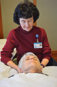 Care Dimensions volunteer Joan Charette giving Reiki to hospice patient at Kaplaln Family Hospice House