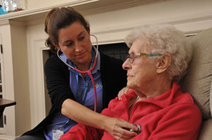 Care Dimensions hospice nurse checks heart of female cardiac patient