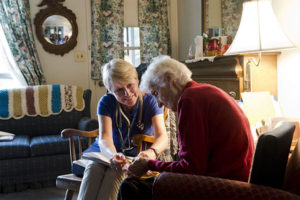 Care Dimensions admissions nurse Kitty Cunningham reviews paperwork with a female hospice patient in her Massachusetts home