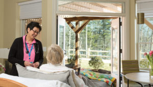 Nurse Trudy Miller speaks with patient at Care Dimensions Hospice House in Lincoln Massachusetts