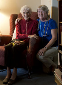 Care Dimensions admissions nurse Kitty Cunningham smiles with a female hospice patient at home