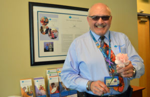Care Dimensions chaplain Bob Hagopian holds a pink carnation like the ones he presented to hospice patients