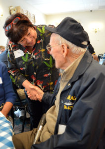 Care Dimensions president Patricia Ahern shakes hand of veteran who volunteers for hospice