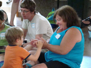 Care-Dimensions-volunteer-Claire-Conway-with-child-at-Camp-Stepping-Stones-grief-support-camp
