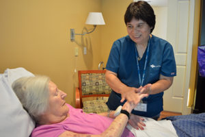 Care Dimensions hospice aide Cindy Berry applies hand lotion for female patient at Kaplan Family Hospice House