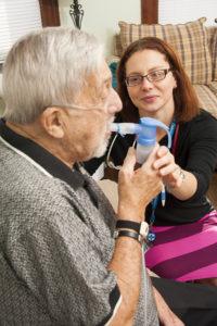 Care Dimensions nurse practitioner Susan Powers assists hospice respiratory patient Tom DeVeau