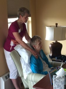 Care Dimensions volunteer Gail Thompson performing Reiki on elderly female hospice patient in chair