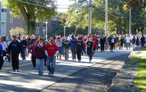 Crowd walking in street at start of Care Dimensions Walk for Hospice
