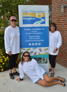 Three members of Swampscott, MA High School Class of 1985 with Care Dimensions Walk for Hospice sign